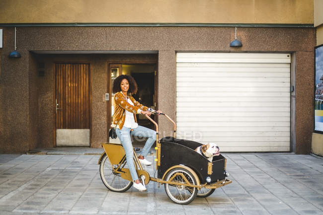 Full length of mid adult woman riding bicycle cart with dog against building — Stock Photo