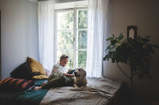 Full length of retired man reading book while resting with dog on bed at home — Stock Photo