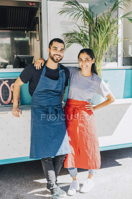 Full length portrait of smiling young colleagues standing against food truck — Photo de stock