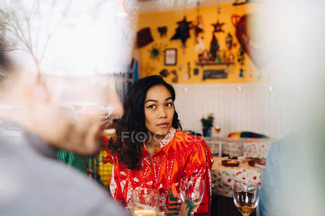 Young woman sitting by female while looking at male friend in restaurant seen through glass window — Stock Photo