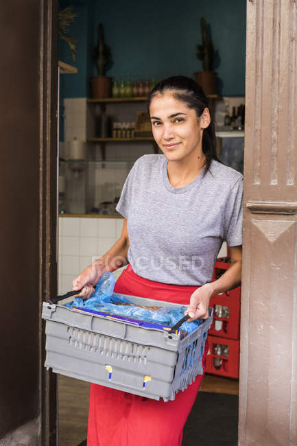 Portrait of confident young female owner standing with crate at restaurant doorway — Stock Photo