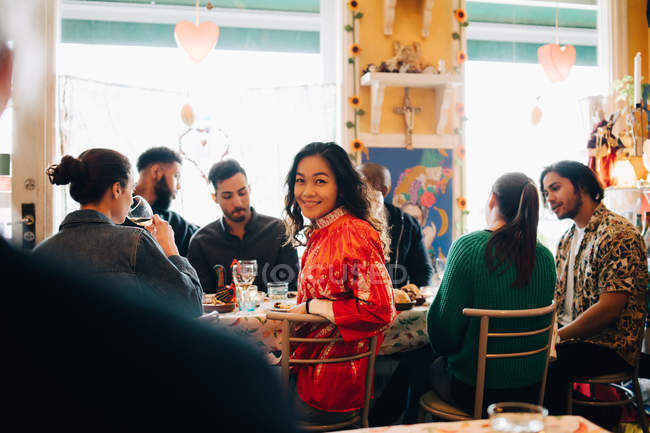 Portrait of smiling young woman sitting amidst multi-ethnic friends during brunch party in restaurant — Stock Photo