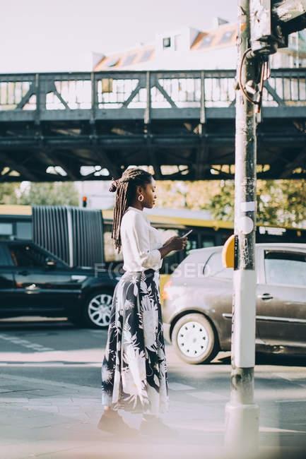 Vista lateral da jovem mulher usando telefone celular enquanto estava na calçada na cidade — Fotografia de Stock