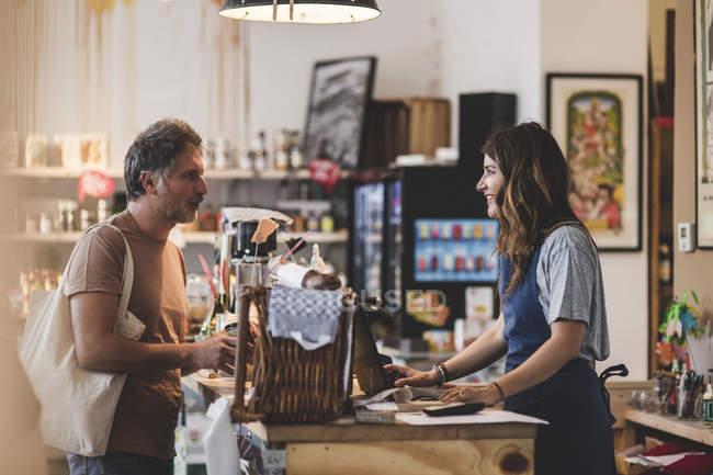 Женщина продаж клерк говорить с клиентом на кассе счетчик в гастрономе — стоковое фото