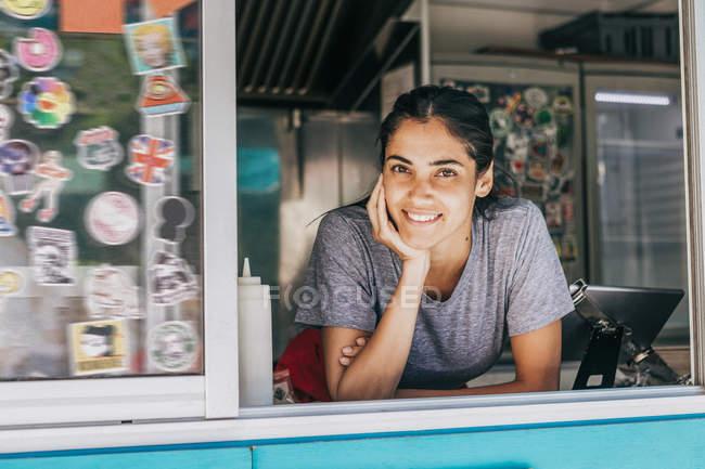 Retrato de una joven vendedora sonriente apoyada en la ventana de un camión de comida - foto de stock