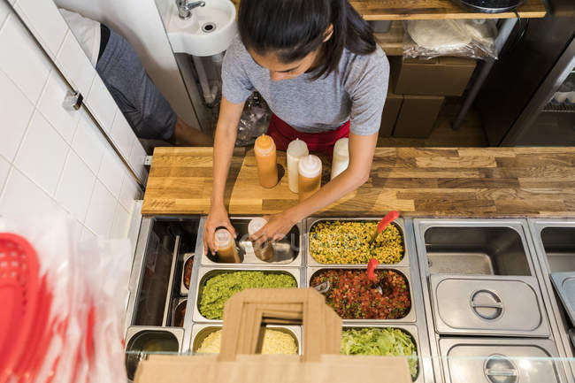 Висококутний вид молодого шеф-кухаря організовує пляшки соусу в контейнері на комерційній кухні. — стокове фото