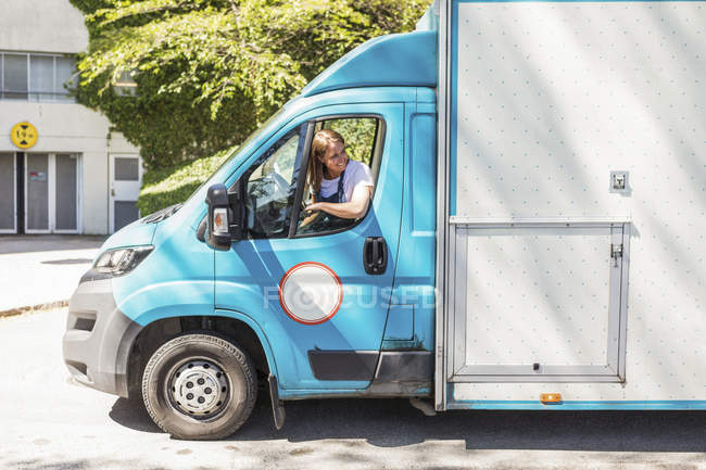 Conduite confiante jeune propriétaire femme camion alimentaire vu par la fenêtre — Photo de stock