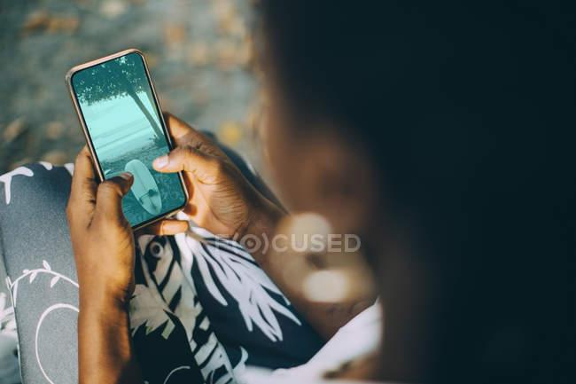 Vista de ángulo alto de la mujer joven que mira la fotografía de la playa en el teléfono inteligente - foto de stock