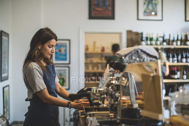 Side view of female sales clerk working at checkout counter in deli — Stock Photo