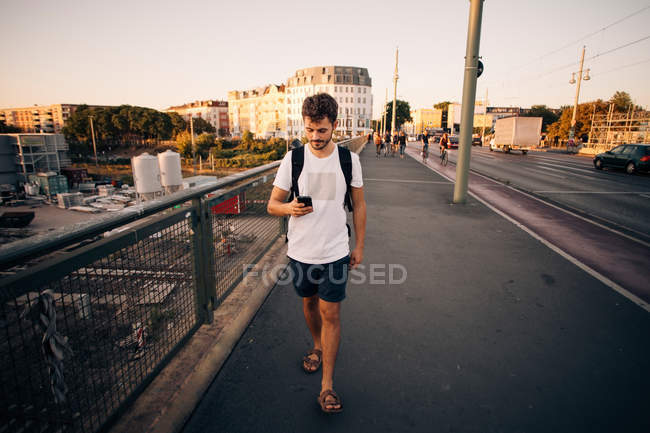 Full length of young man using mobile phone while walking on footpath at bridge in city — Stock Photo