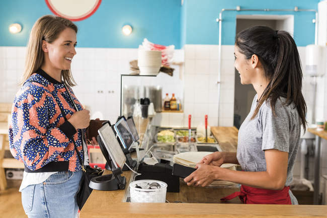 Side view of smiling female customer and owner talking while standing at checkout in restaurant — Stock Photo