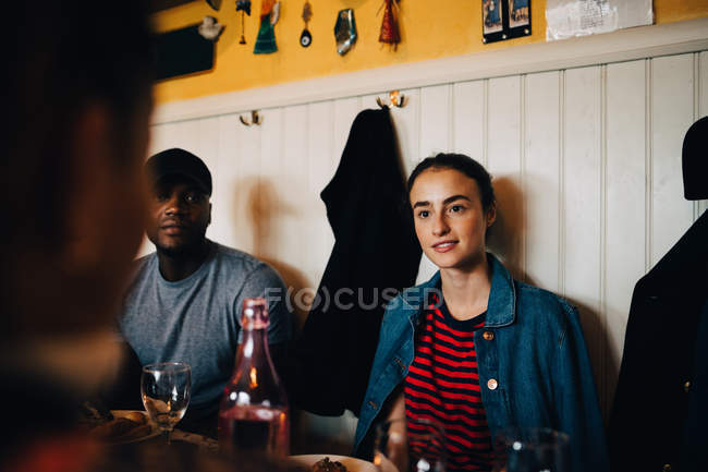 Young woman sitting by man while looking at female friend in restaurant during dinner party — Stock Photo