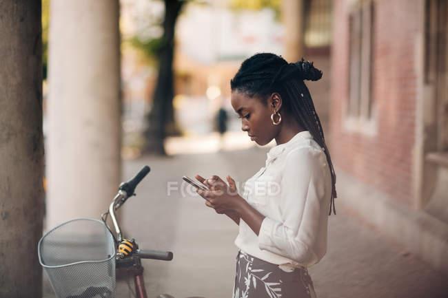 Вид сбоку на молодую женщину, использующую мобильный телефон, стоя на велосипеде на пешеходной дорожке в городе — стоковое фото