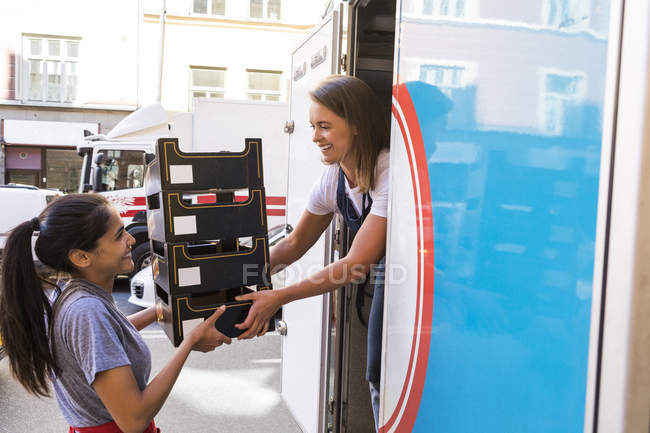 Smiling female colleagues loading food truck with containers in city — Stock Photo