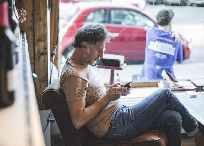Mature owner using mobile phone while sitting on chair in deli — Stock Photo