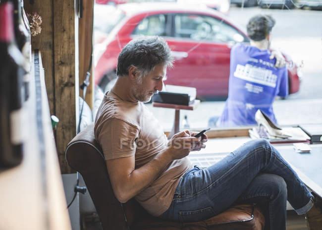 Propriétaire mûr utilisant le téléphone portable tout en s'asseyant sur la présidence dans la diure — Photo de stock