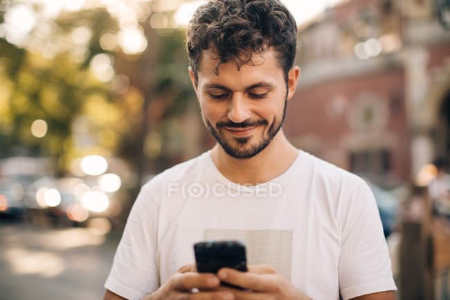 Smiling young man using smart phone while standing on street in city — Stock Photo