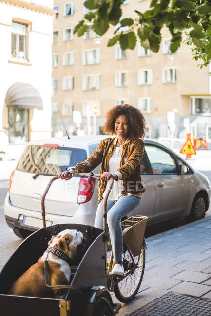 Full length of happy woman riding bicycle cart with bulldog on sidewalk by car in city — Stock Photo
