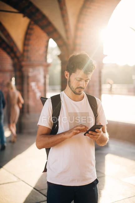 Jovem usando telefone inteligente enquanto está em pé no caminho da cidade — Fotografia de Stock