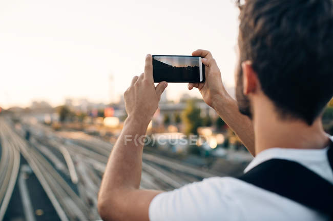 Young man photographing through smart phone over railroad tracks in city — Stock Photo