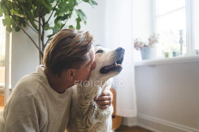 Primer plano de hombre senior jubilado besos retriever sentado en casa - foto de stock