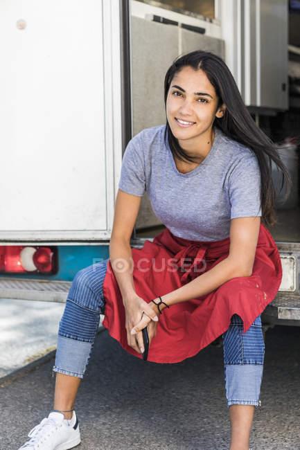 Retrato de una joven propietaria confiada sentada en la entrada de un camión de comida - foto de stock