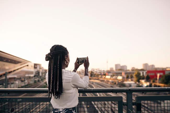 Молодая женщина фотографирует через мобильный телефон, стоя на мосту под ясным небом — стоковое фото