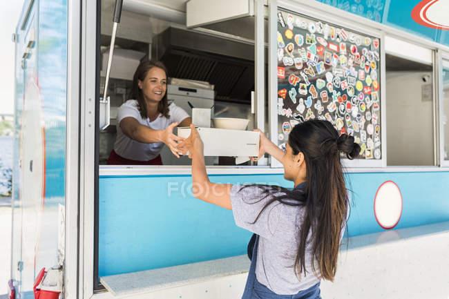 Lächelnde junge multiethnische Inhaberin übergibt Container an Verkäuferin auf Food-Truck — Stockfoto
