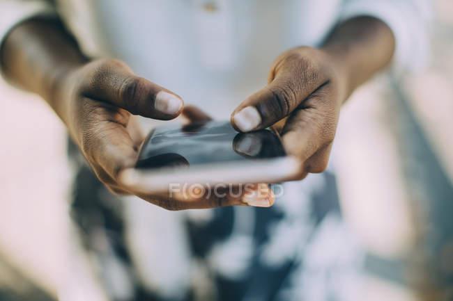 Midsection de mujer joven usando el teléfono inteligente mientras está parado al aire libre - foto de stock