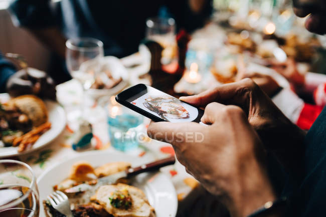 Cropped image of young man photographing food in plate at restaurant — Stock Photo