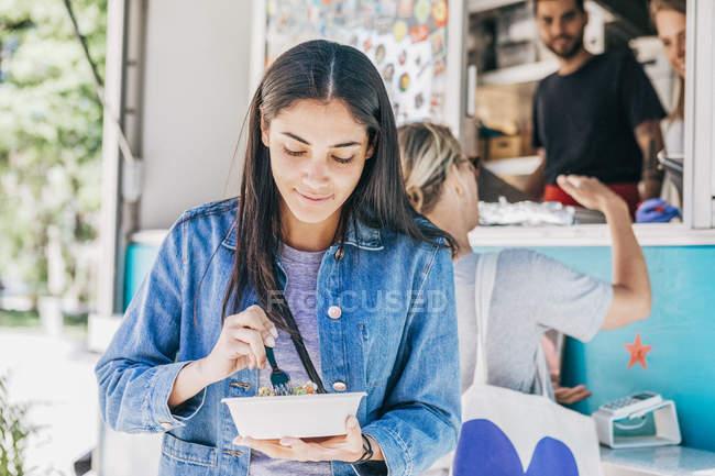 Mujer joven comiendo fresco Tex-Mex en tazón contra camión de comida - foto de stock