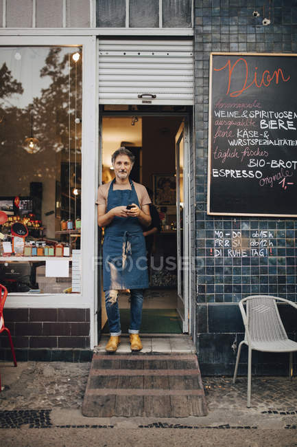 Portrait of male owner standing at entrance of deli — Stock Photo