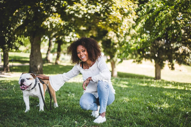 Portrait of smiling woman with bulldog on grassy field at park — Stock Photo