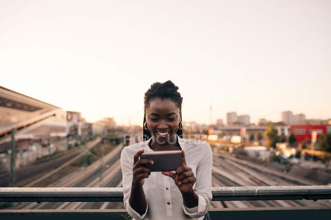 Улыбающаяся молодая женщина, фотографирующая через мобильный телефон, стоя на мосту под ясным небом в городе — стоковое фото