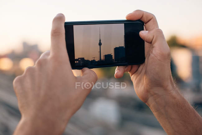 Cropped image of young man photographing Fernsehturm through smart phone during sunset — Stock Photo