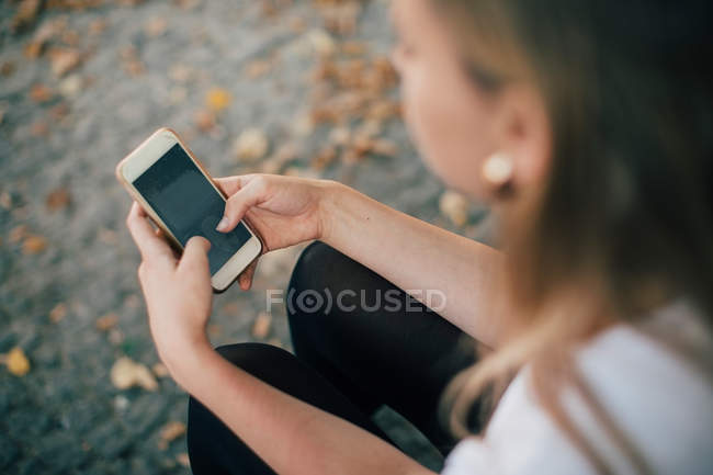 High angle view of young woman using mobile phone while sitting on footpath — Stock Photo