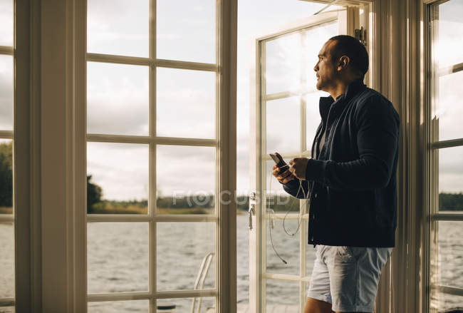 Nachdenklicher älterer Mann benutzt Handy, während er in Ferienvilla vor der Tür steht — Stockfoto
