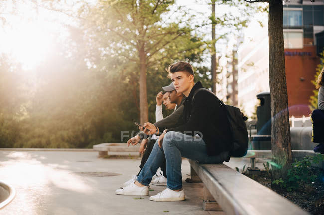 Full length of friends using mobile phone while sitting on retaining wall — Stock Photo