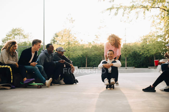 Friends looking at smiling woman pushing cheerful man sitting on skateboard at park — Stock Photo