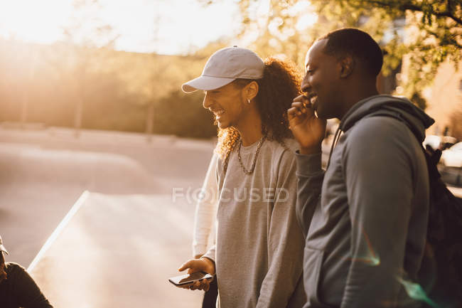 Happy friends talking to man at skateboard park — Stock Photo