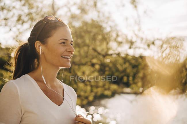 Усміхаючись зрілої жінки говорив через навушники в літні канікули — стокове фото