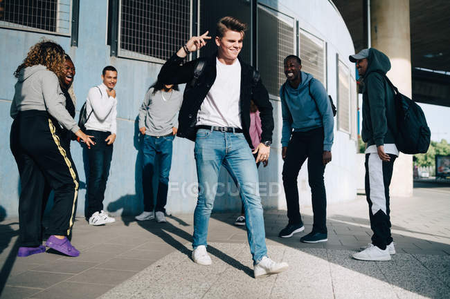 Cheerful friends looking at young man standing on sidewalk in city — Stock Photo