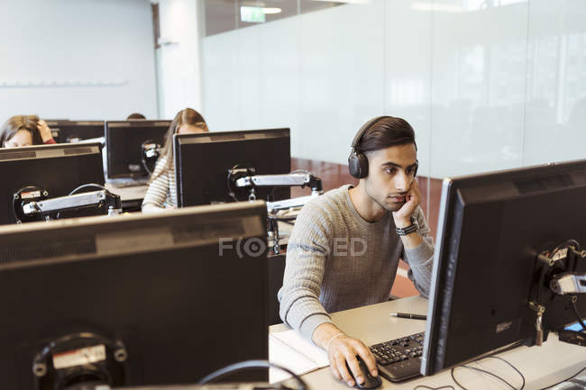 Young male student wearing headphones while using computer at university library — Stock Photo