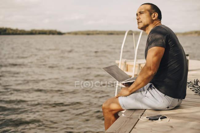 Pensativo maduro homem sentado com laptop no molhe sobre lago — Fotografia de Stock