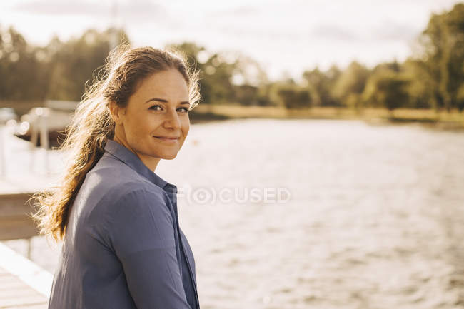 Portrait of smiling mid adult woman by lake during sunny day — Stock Photo