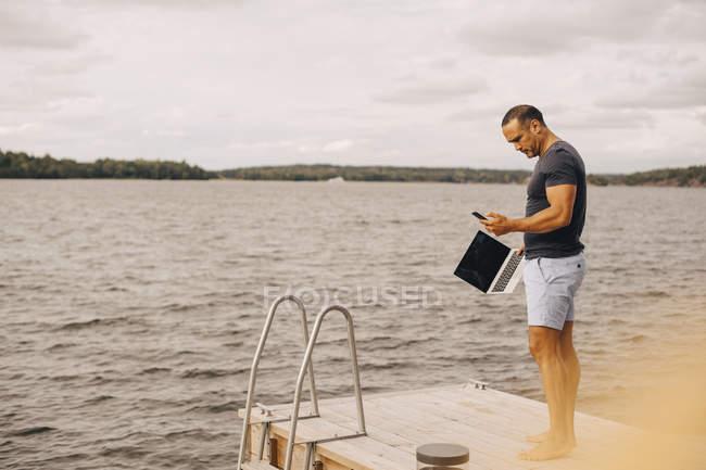 Comprimento total do homem com laptop usando telefone enquanto está em pé no molhe contra o céu — Fotografia de Stock