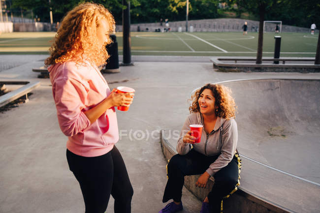 Smiling young women talking while having drinks at skateboard park — Stock Photo