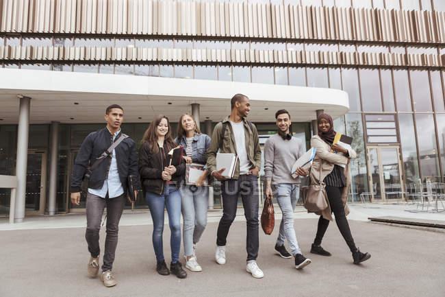 Tutta la lunghezza degli studenti universitari multietnici che camminano contro l'edilizia nel campus — Foto stock