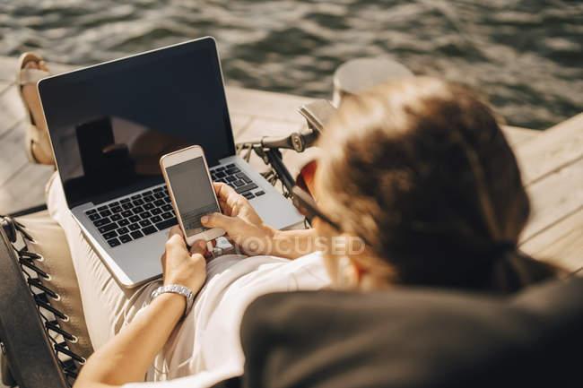 Vue d'angle élevé de femme avec messagerie sur téléphone intelligent tout en étant assis à la jetée de texte portable — Photo de stock
