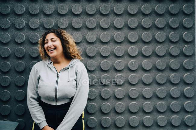 Mujer alegre con los ojos cerrados de pie contra la pared gris - foto de stock